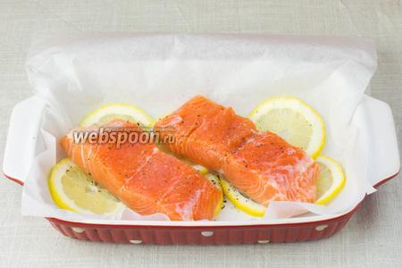 Форму застелить пергаментной бумагой. На дно выложить лимонные кружочки, сверху положить рыбу, предварительно удалив из неё кости и шкуру. Посолить и поперчить.