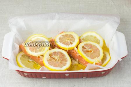 На рыбу выложить лимон и полить заправкой.