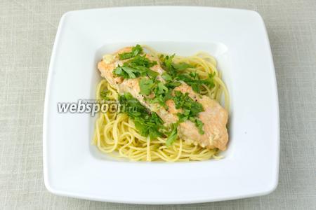 Пасту подавать отдельными порциями. В терелку выложить спагетти, сверху положить кусочек рыбы и посыпать петрушкой.