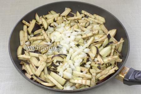 В сковороде разогреть растительное масло, добавить баклажаны и лук. Жарить овощи 5 минут, постоянно перемешивая.