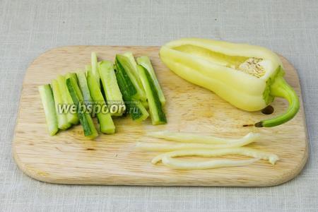 Огурцы и перец нарезать тонкой соломкой.