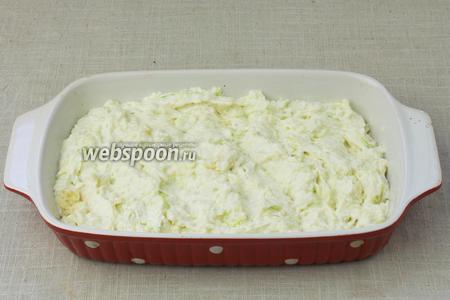 Затем взять форму для выпекания и смазать её подсолнечным маслом. Добавить в форму тесто, равномерно распределить и уплотнить влажными руками.
