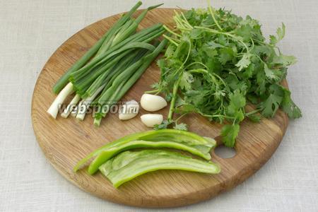 Кинзу, зелёный лук и перец промыть и обсушить при помощи салфеток. Чеснок очистить от кожуры. Часть кинзы и зелёного лука отложить. Горький перец разделить пополам, удалить из него семена и белую часть.