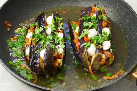Начинить жаренными овощами баклажаны, вложить в каждую борозду сыр и посыпать зеленью. Баклажаны переложить обратно в сковороду, добавить немного кипячёной воды, чтобы покрыть дно. Сковороду накрыть крышкой и поставить на слабый огонь тушиться 10-15 минут.