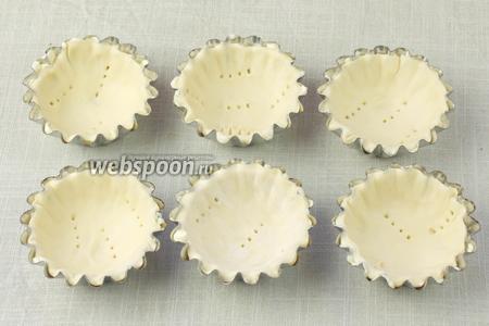 Тесто немного раскатать и с помощью стакана вырезать кружочки около 10 сантиметров в диаметре. Формочки щедро смазать сливочным маслом (силиконовые смазывать не надо) и выстлать их тестом. Проколоть в 2-3 местах вилкой. Поставить на 30 минут в холодильник.  Из 400 грамм слоёного теста должно получиться 15 корзинок, если взять формочки 7 сантиметров в диаметре.