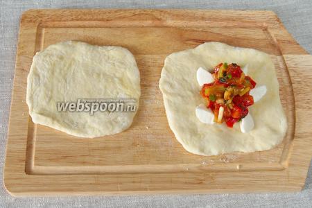Раскатать каждую порцию в небольшой квадрат, разложить начинку из Моцареллы и тушёных овощей. Соединить четыре угла друг с другом и тщательно прижать.