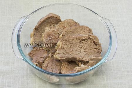Варёное мясо нарезать кусочками в 2 см толщиной. Выложить в огнеупорную форму и немного посолить.