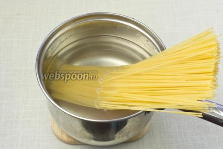 В кастрюлю влить большое количество воды, сразу посолить и отварить спагетти «аль денте».