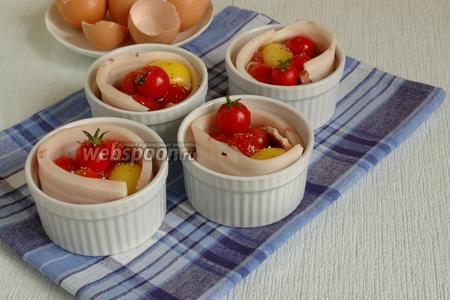 Выбить сверху яйца, также положить ещё по одному помидору черри (с хвостиками, для красоты). Приправить свежемолотой смесью перцев. Можно ещё посолить сверху, если нужно.