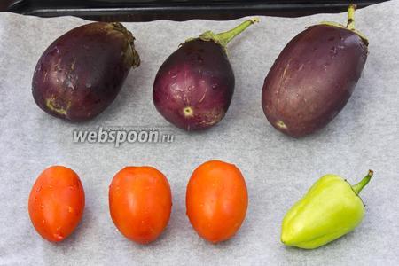 Баклажаны, томаты и перец помыть. Выложить на противень, устеленный пергаментной бумагой. Отправить запекаться в разогретую до 160 °C духовку.