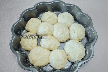Скатать круглые булочки. Равномерно разложить их в форму. Накрыть салфеткой. Поставить в тёплое ещё на 30 минут.