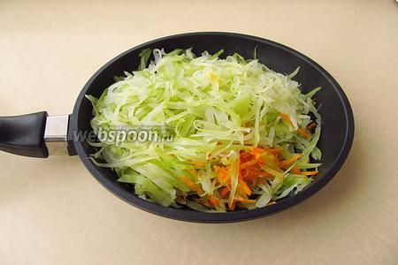 Соединить капусту с морковью и луком, закрыть сковороду крышкой и потомить на слабом огне в течение 7–8 минут.