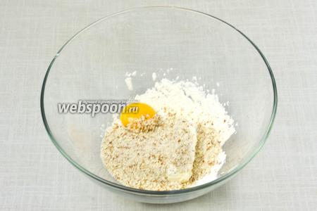 В глубокой миске смешать молотый миндаль, муку, ванильный сахар, размягчённое сливочное масло и желток 1 яйца (белок не требуется). Массу тщательно перемешать вилкой или венчиком.