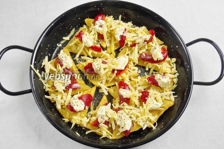 Обсушенные чипсы уложить на противень, на каждую выложить чайную ложку густой сметаны или сливок, нарезанные куски сладкого перца, сверху засыпать тёртым сыром. Поставить в горячую духовку на 3 минуты.