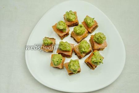 Авокадо почистить. Пюрировать с 1 ч. л. оливкового масла, мелко нарезанной зелени, немного соли и перца. Разложить пюре авокадо на ломтики сёмги.