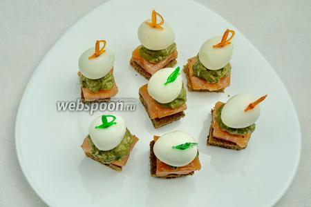 Перепелиные яйца очистить. Нанизать на шпажку и воткнуть в хлебец канапе. Украсить семенами кунжута. Подавать готовые канапе на закуску.