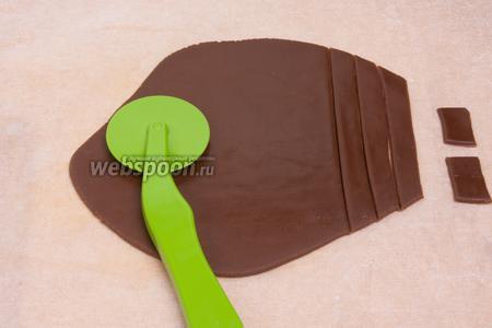 На пергаментной бумаге раскатать тонко мастику и с помощью ножа вырезать прямоугольники. Это будет черепица для крыши.