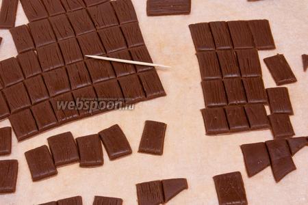 Далее шоколадным прямоугольникам придать с помощью зубочистки текстуру черепицы или дерева.