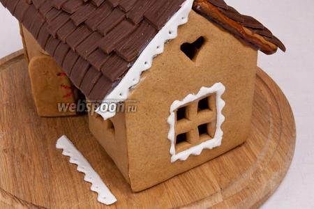 Затем украсить домик белой мастикой. Подчеркнуть окна и скрыть места соединения пряника и карамели. Крепить можно  используя айсинг или сгущённое молоко.
