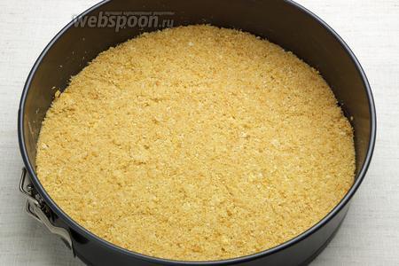 Выложить крошку из крекера — утрамбовать стаканом, формируя корж-основу.