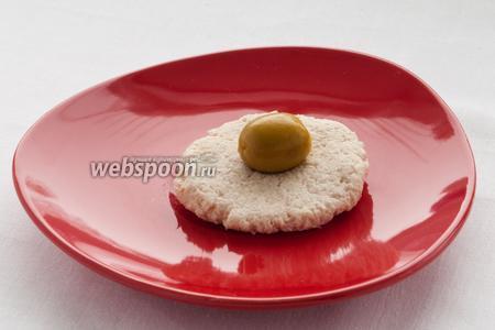Из получившейся массы слепите небольшую лепёшку и положите в центр оливку.