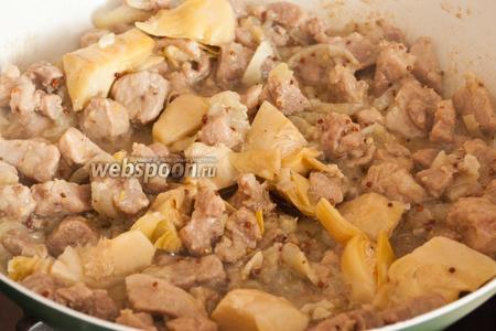 Добавьте артишоки и помешивая продолжайте обжаривать мясо ещё 5-7 минут, до золотистой корочки.