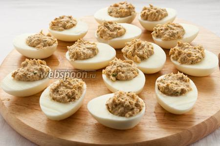 Незадолго до сервировки стола начините яйца полученным паштетом, при помощи двух чайных ложек (счищайте шарик из начинки одной ложкой об другую, тем самым выкладывая его в яичный белок).