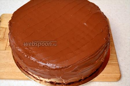 Перемажьте шоколадом оставшиеся два коржа, а также обмажьте его по бокам. Дайте шоколаду застыть в холодильнике и украсьте торт по своему усмотрению.