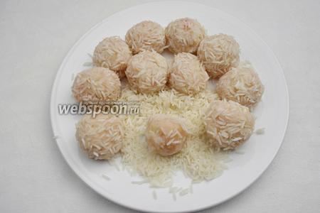Рис промыть. Очень хорошо просушить в льняной салфетке. Высыпать рис на тарелку, обвалять мясные шарики в рисовых зёрнах, плотно прижимая их руками к мясу.