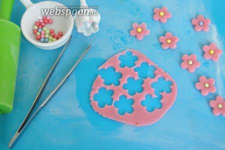 Для приготовления цветочков раскатать мастику и вырезать плунжерами цветы нужной формы. Серединку смазать сиропом и прижать бусинку кондитерскую. Готовые цветы выложить сохнуть на 1 день.