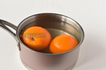 Поместить апельсины в воду. Довести до кипения. Проварить 5 минут. Воду слить. Такую процедуру повторить 3 раза. Четвёртый раз проварить апельсины 15 минут. Воду слить.