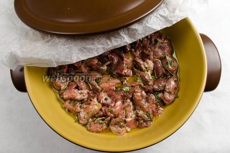 Залить оливковым маслом (масло должно полностью покрыть мясо). Накрыть форму листом бумаги для выпечки, предварительно смяв его, а затем крышкой и поставить в духовку на 45 минут.