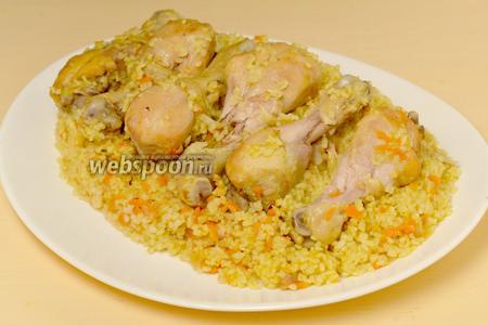 Готовый булгур выкладываем в большое блюдо и сверху кладём куриные голени. Салат из свежих овощей и зелени к этому блюду очень подойдёт.