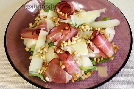 Сыр натереть на тёрке или нарезать стружкой. Присыпать поджаренными орешками.