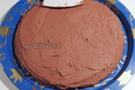 Кладём на блюдо один корж и покрываем половиной крема.