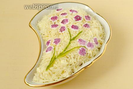 На поверхности салата выкладываем веточку сакуры из подготовленных цветков, тонкие веточки вырезаем из свежего или консервированного огурца. У цветущей сакуры листьев не бывает, они появляются после цветения, поэтому зелень здесь не используем.  С помощью чистой художественной кисти наносим на каждый цветок немного свекольного сока, разведённого водой, чтобы цвет получился розовым, а не тёмно-бордовым. Подаём салат сразу.