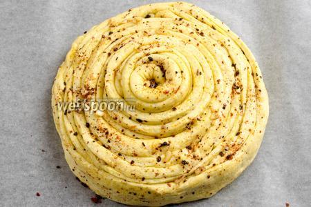 В результате получить круглую буханку в виде конуса, возвышающегося в центре. Выложить её на пергаментную бумагу на противень. Смазать остатками оливкового масла. Поставить в горячую духовку. Выпекать хлеб 30 минут при температуре 200 °C.