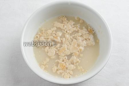 Смешать дрожжи с сахарной пудрой. Залить небольшим количеством тёплой воды. Оставить на 5-10 минут в тепле.
