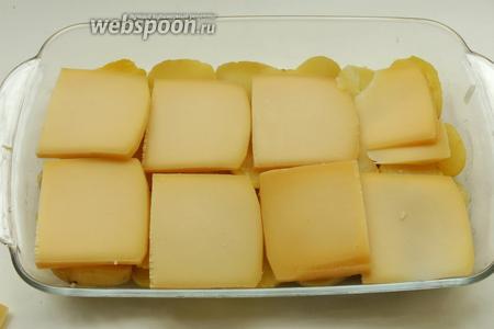 Сыр Раклет режем на 8 пластинок и кладём сверху на картофель.