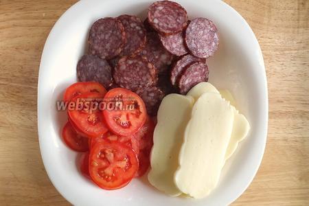Нарежьте моцареллу ломтиками, салями и помидоры — тонкими кружочками.