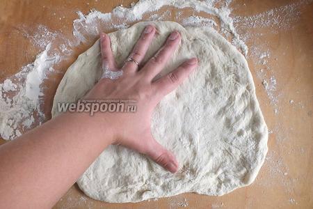 Разогрейте духовку до 220-240°C. Во время разогревания, поставьте на дно ёмкость с водой, при выпекании пиццы, воду нужно убрать. Разделите подготовленное тесто на 3 части, немного обомните и начинайте аккуратно растягивать тесто руками в лепёшку нужной формы. Если сложно — используйте скалку. Каждый круг я раскатываю диаметром около 25-26 см.