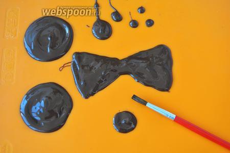 На силиконовом коврике нарисуем карандашом два одинаковых кружочка диаметром 4-5 см, это ушки мишки. Можно просто обвести рюмку нужного диаметра. От руки нарисуем бабочку, кружочек для носа и зрачки. Зрачков сделайте несколько про запас, вдруг понадобится. В центр кружочков с ложки льём шоколад, и кисточкой разравниваем его по окружности, постепенно увеличивая радиус. Заполним шоколадом контур бабочки. Сделаем точки-зрачки и носик. Отправим всё в холод минут на 20.
