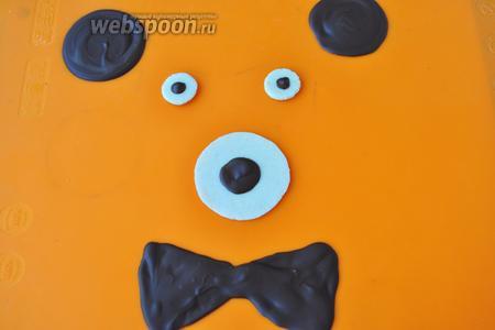 Когда шоколадный декор застыл, кладём шоколадные зрачки на белые кружочки и так же делаем мордочку. Мишка готов, можно пока эти детали положить в холод. Приступим к приготовлению крема.