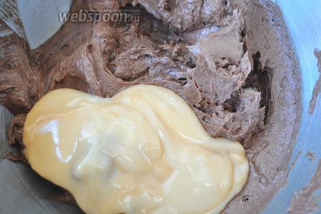 Добавить в желтки масло и какао и взбить. Положить сгущёнку и взбивать до однородности.
