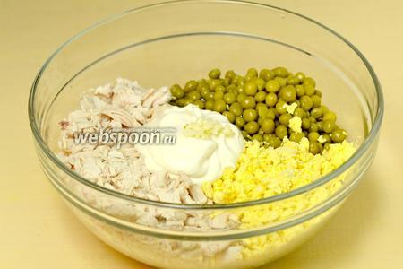 Добавляем к курице зелёный горошек, раскрошенный желток вареных яиц, майонез и выдавленный чеснок (один зубчик), смешиваем.