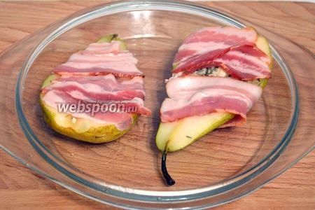 Оберните каждую половинку груши полосками бекона. И отправьте в разогретую до 180°C духовку на 15 минут, затем ещё пару минут подержите под грилем для образования корочки.