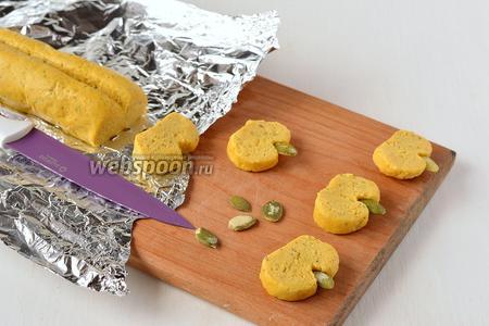 Развернуть тестяную заготовку и нарезать острым ножом печенье толщиной 1 см. Печенье выйдет в виде небольших тыковок. Прикрепить тыквенные семечки к каждому печенью.