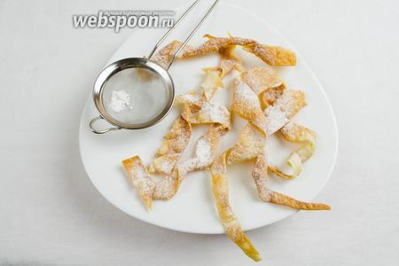 Разложить готовое остывшее печенье небольшими порциями на широкую тарелку. Посыпать его сахарной пудрой.