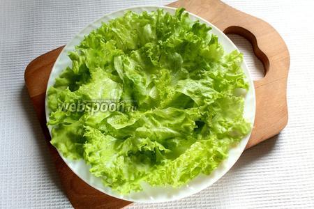Порвать листья салата и уложить на тарелку.