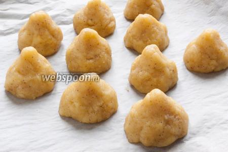 Из полученного теста скатать небольшие шарики и, слегка прижимая их, придать печенью коническую форму. Выложить на противень, застеленный пергаментной бумагой. Выпекать при 170°C около 15 минут.